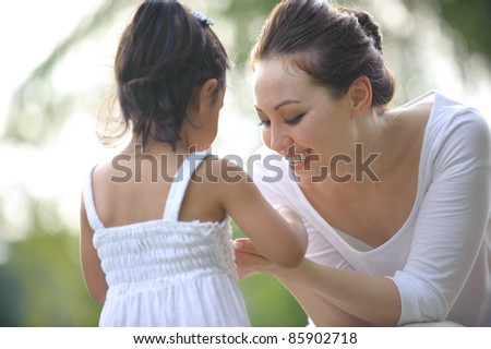 Mum and daughter spending time together in the park - stock photo
