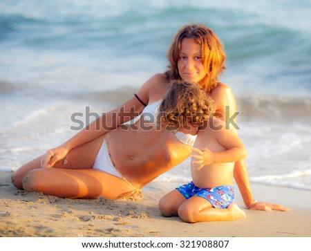 Mum and is son on the beach in the sunset - stock photo