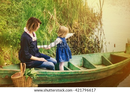 Mum and small baby sitting together in old wooden boat on river. Baby pointing with finger at something on water. Happy family in scenic nature place. Picnic during vacations. - stock photo