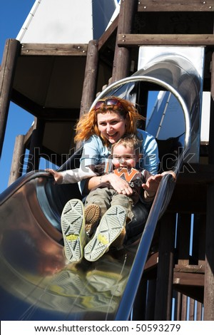 Mum and the son cheerfully go for a drive on a children's hill - stock photo