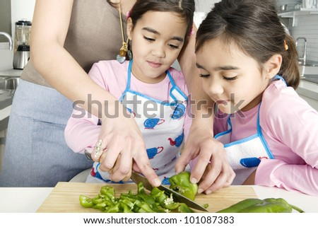 Mum chopping vegetables with twin daughters in a family home kitchen. - stock photo