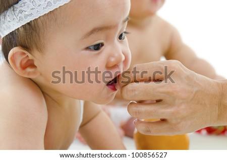 Mum feeding Asian baby snacks - stock photo