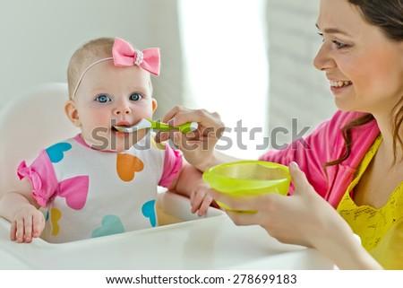 Mum feeds the child - stock photo