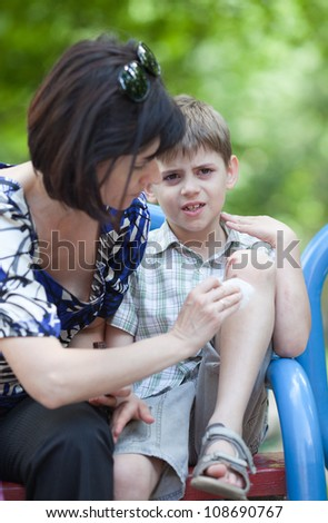 Mum helping her son who scraped his knee - stock photo