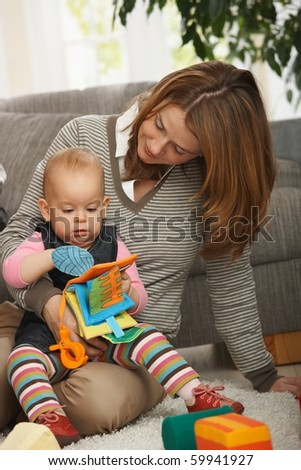 Mum holding baby daughter playing together with toys on living room floor.? - stock photo