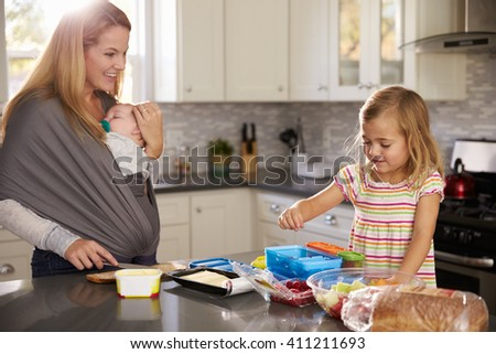 Mum holding baby watches older daughter preparing food - stock photo
