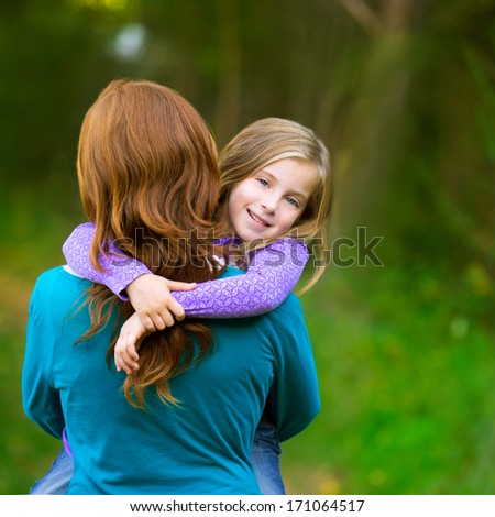Mum holding daughter kid girl in her arms rear view smiling in outdoor - stock photo