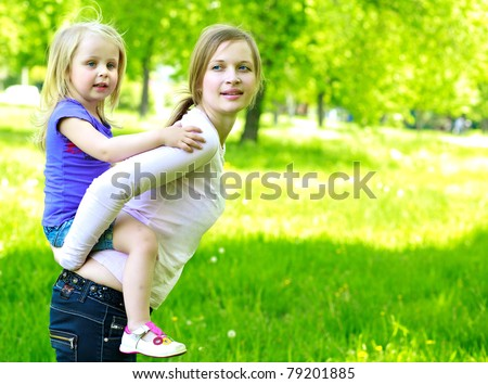 Mum holds the small daughter outdoors smiling - stock photo