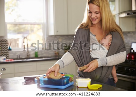 Mum preparing lunchbox while baby sleeps on her in a carrier - stock photo