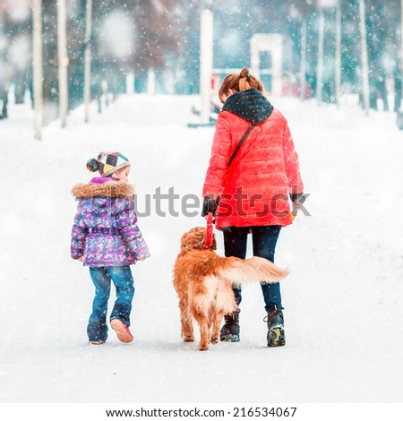mum with a daughter and their dog walking in winter park - stock photo