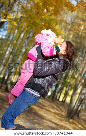 Mum with a daughter walk in autumn park - stock photo