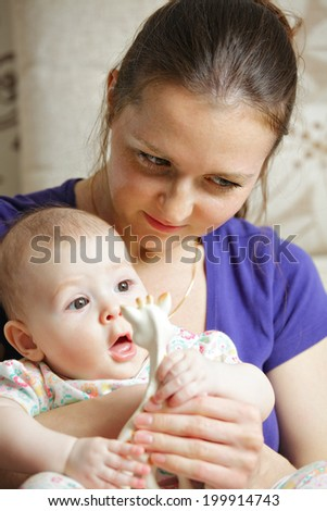 Mum with her baby on hands both looking sideways - stock photo