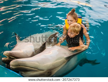 Mum with kid floats with dolphins in pool - stock photo