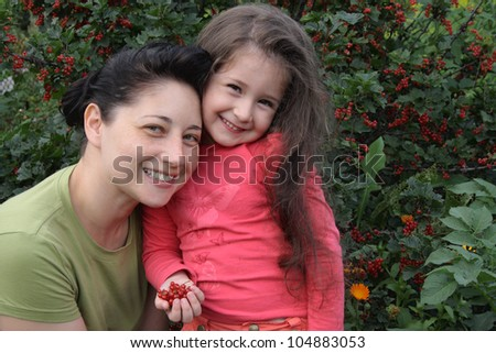 Mum with the daughter on a background of a bush of a red currant - stock photo