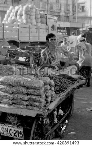 MUMBAI, INDIA - FEBRUARY 15, 1984: guy selling coal in the biggest open air city market. The place is everyday populated by thousands of people. - stock photo