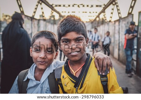 MUMBAI, INDIA - 12 JANUARY 2015: Indian school boys on bridge in Dharavi slum. Post-processed with grain, texture and colour effect. - stock photo