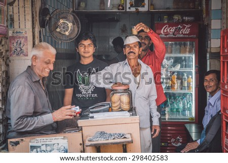 MUMBAI, INDIA - 17 JANUARY 2015: Indian workers pause for photo and have fun. Post-processed with grain, texture and colour effect. - stock photo