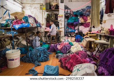 MUMBAI, INDIA - 12 JANUARY 2015: Two men work in small underwear factory in Dharavi slum. Dharavi is one of the largest slums in the world. - stock photo