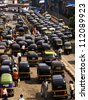 MUMBAI, INDIA-JULY 17: Crowd and traffic jam on the outer local street. The street is full with classic auto rickshaws on July 17, 2008 in Mumbai, India. - stock photo