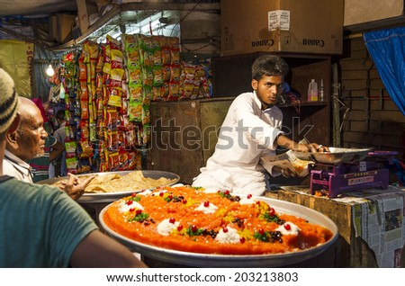 Mumbai, India - July 3, 2014 -  Man selling snacks from stall at at crowded Mohammad Ali Road in the evening during Ramzan fasting month - stock photo