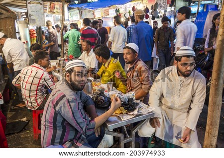 Mumbai, India - July 3, 2014 - Muslim people eating dinnerfrom food stall at crowded Mohammad Ali Road in the evening during Ramzan fasting month - stock photo