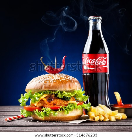 MUMBAI, INDIA  MAY 23, 2015: Illustrative editorial veggie burger, French fries and Coca-Cola bottle - is the most popular carbonated soft drink beverages sold around the world - stock photo