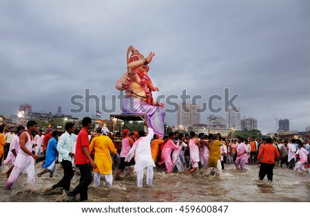 Mumbai, India - 14 SEPTEMBER 2015 - Crowds on the beach watching devotees pushing Hindu God Ganesha into the ocean - stock photo