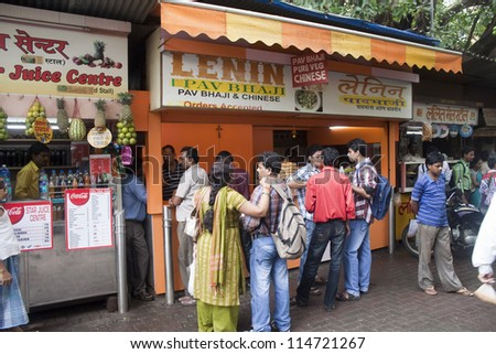 MUMBAI, INDIA - SEPTEMBER 6: Unidetified locals eat at street food stalls on September 6, 2011 in Mumbai, India. Mumbai is famous for its street food. Stalls offer  delightful variety of meals. - stock photo