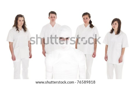 Mummyfied Patient in front of Healtcare Staff isolated on white background - stock photo