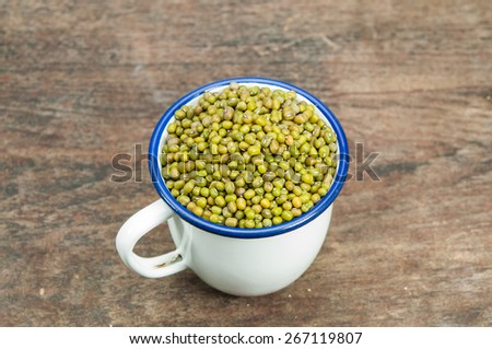 mung beans in white cup on wooden table. - stock photo