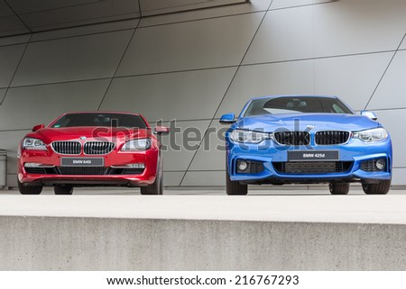 MUNICH, GERMANY - AUGUST 9, 2014: Latest generation of new model lineup BMW luxury cars. Wet after rain two 640i and 425d front view. - stock photo