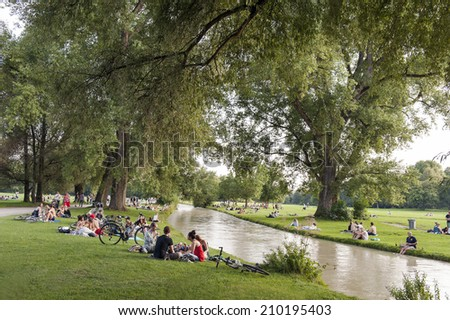 MUNICH - GERMANY- AUGUST 6, 2014 People sunbathing in English Garden, Munich, Bavaria, Germany, Europe - stock photo