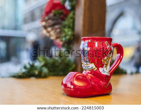 MUNICH,GERMANY- DEC 19:A wine cup in shape of a boot is on a wooden desk outside, during a traditional Christmas market in Munich,Germany on 19 December 2014. Such cups are used to drink mulled wine. - stock photo