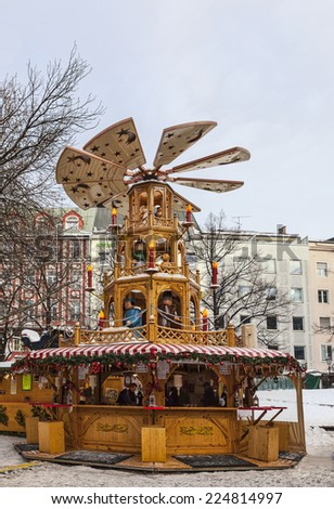 MUNICH,GERMANY- DEC 19: Traditional wooden carousel located outside in a traditional Christmas market in Munich,Germany on 19 December 2014.  - stock photo