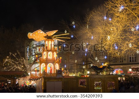 MUNICH, GERMANY - DECEMBER 12: Traditional christmas market at night with a illuminated pyramid in Munich, Germany on December 12, 2015. Foto taken from Rindermarkt. - stock photo