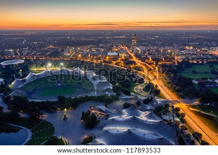 MUNICH, GERMANY - OCTOBER 2: Cityscape of Munich at dusk from the Olympiapark on October 2, 2012. The Olympiapark is an Olympic Park which was constructed for the 1972 Summer Olympics. - stock photo