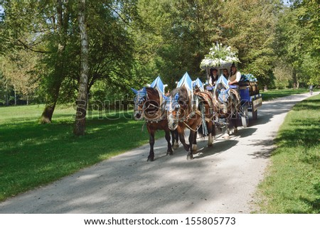 MUNICH, GERMANY - SEPT. 24, 2013: Hofbrau Beer Carriage on Route through the English Garden to the annual Oktoberfest.  The Festival runs from Sept. 21 -Oct. 6  in Munich, Germany - stock photo
