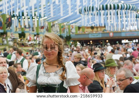 MUNICH, GERMANY - SEPT. 21, 2014:  Oktoberfest Crowds of visitors at the Spatenbrau Tent celebrating the festivities with Smiling Waitress. The Festival runs from Sept. 20 - Oct. 5  in Munich, Germany - stock photo