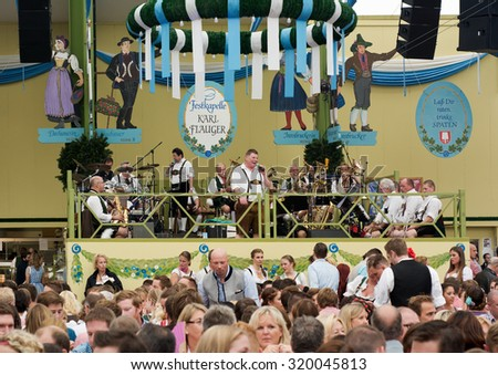 MUNICH, GERMANY - SEPT. 19, 2015:  Oktoberfest Visitors Enjoy Traditional Music and Beer in the Spatenbrau Tent. The Festival runs from September 19th until October 4th 2015 in Munich, Germany. - stock photo