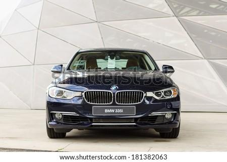 MUNICH, GERMANY - SEPTEMBER 19, 2012: New model BMW 335i in dark blue against modern design surface. - stock photo