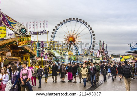 MUNICH, GERMANY - SEPTEMBER 22, 2012: Oktoberfest Munich: The big Ferris wheel. In the foreground people are walking between beer tents and fairground attractions. - stock photo