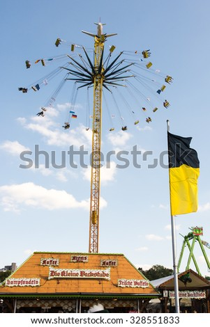 MUNICH, GERMANY - SEPTEMBER 30: People in a chairoplane on the Oktoberfest in Munich, Germany on September 30, 2015. Oktoberfest is the biggest beer festival of the world with over 6 million visitors - stock photo
