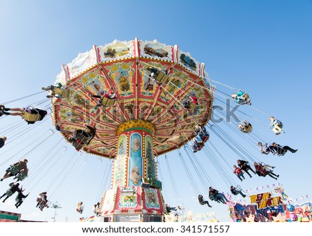 MUNICH, GERMANY - SEPTEMBER 30: People in a chairoplane on the Oktoberfest in Munich, Germany on September 30, 2015. The Oktoberfest is the biggest beer festival of the world. - stock photo