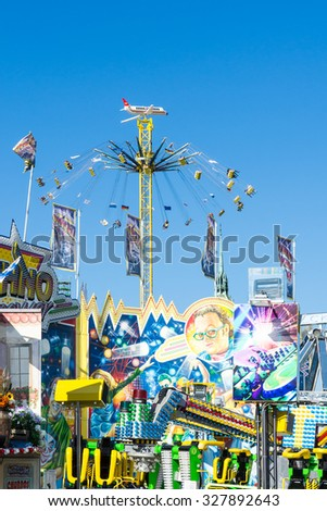 MUNICH, GERMANY - SEPTEMBER 30: People in a high chairoplane on Oktoberfest in Munich, Germany on September 30, 2015. Oktoberfest is the biggest beer festival of the world with over 6 million visitors - stock photo