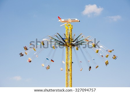 MUNICH, GERMANY - SEPTEMBER 30: People in a high chairoplane on the Oktoberfest in Munich, Germany on September 30, 2015. The Oktoberfest is the biggest beer festival of the world. - stock photo