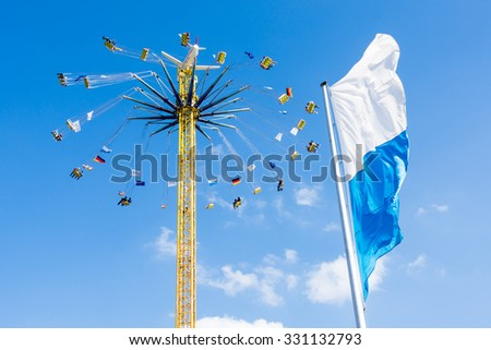 MUNICH, GERMANY - SEPTEMBER 30: People in a high chairoplane on the Oktoberfest in Munich, Germany on September 30, 2015. The Oktoberfest is the biggest beer festival of the world - stock photo