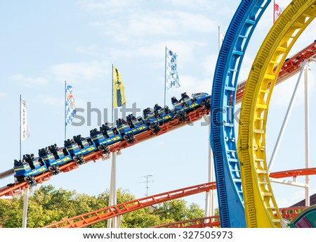 MUNICH, GERMANY - SEPTEMBER 30: People in a roller coaster on Oktoberfest in Munich, Germany on September 30, 2015. Oktoberfest is the biggest beer festival of the world with over 6 million visitors. - stock photo