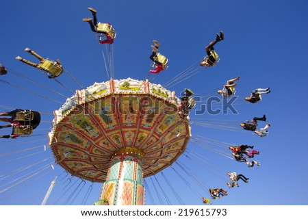 MUNICH, GERMANY - SEPTEMBER 23, 2014: The Oktoberfest in Munich is the biggest beer festival of the world. The visitors have lot of fun with many amusement huts and big carousels. - stock photo