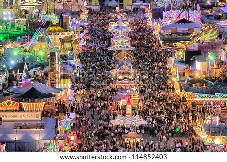 MUNICH - SEPTEMBER 28: Large numbers of tourists and locals come to see the attractions of the world's famous fun fair and beer festival Oktoberfest in Munich, Germany at night on September 28, 2012. - stock photo