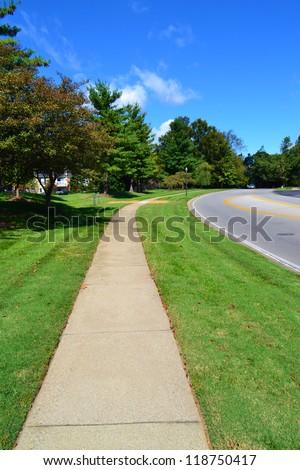 Municipal Sidewalk Follows Alongside a Local Roadway - stock photo
